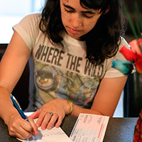 teenager writing at a table