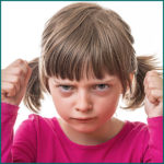 unhappy little girl making fists